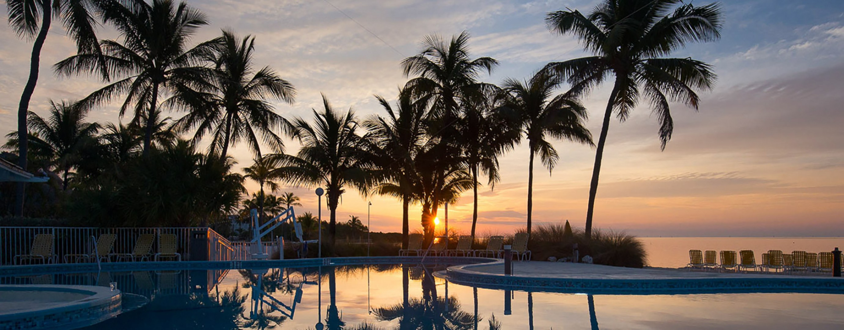 Sunset at the pool of Postcard Inn Beachfront Resort & Marina